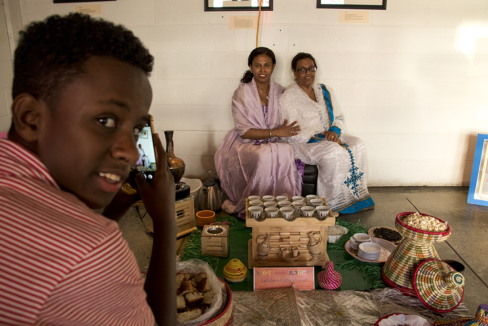 Sara Gebre's eldest son, Matthew, photographs his mother (center) and grandmother, Mulu. Ethiopian coffee service gets kicked off at Comal Kitchen, Dec. 14, 2017. (Kevin J. Beaty/Denverite)  denver; colorado; denverite; kevinjbeaty; comal kitchen; food; globeville; taxi;
