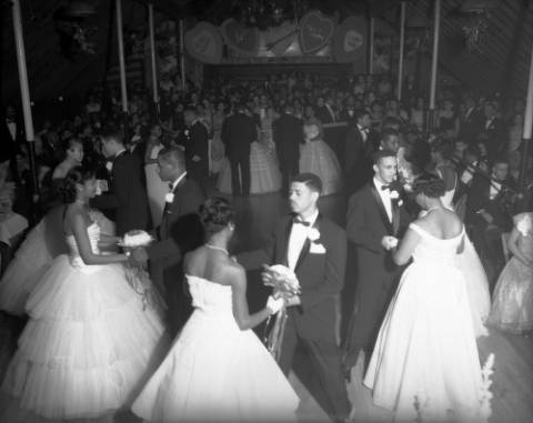 """View of an Owl Club function. A group of African American (Black) teenagers stand in a circle on a ballroom floor in Denver, Colorado. The young women wear formal dresses and the young men wear tuxedos. Other couples crowd the room. Decorations in the distance read: """"Be My Valentine"""" """"Love"""" and """"I Love You."""" (Burnis McCloud/Denver Public Library Western History Collection/MCD-223)"""