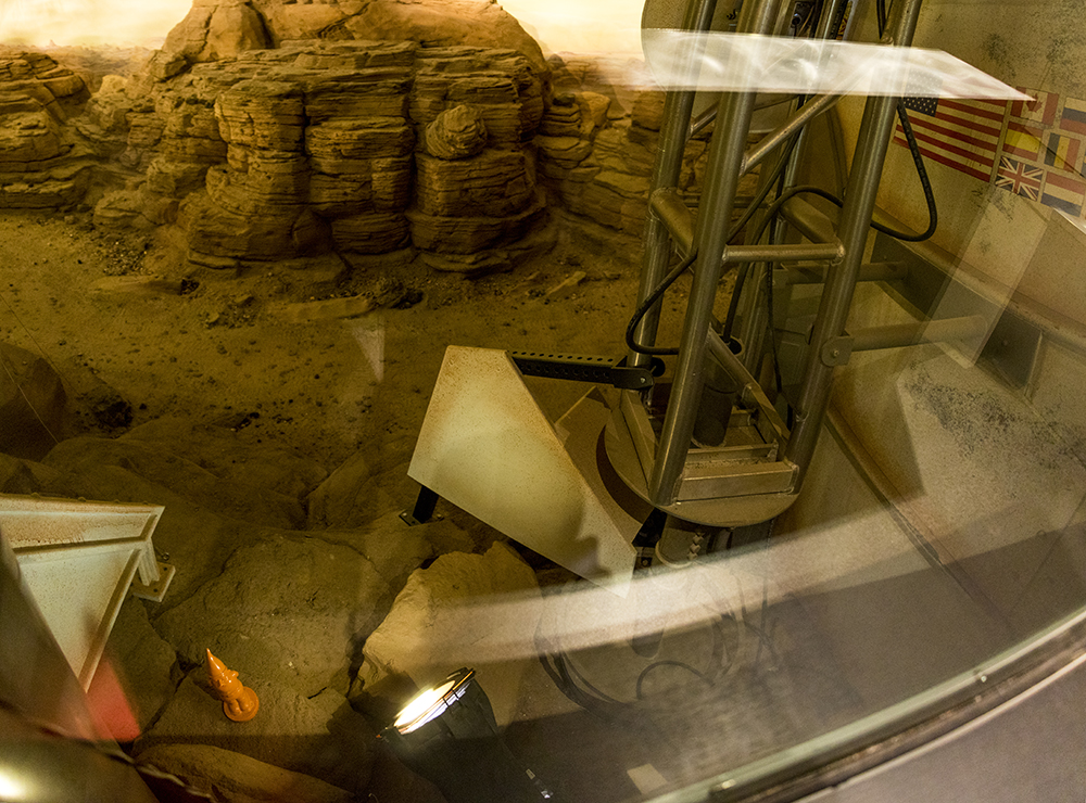 A little orange gnome is hidden among red rocks at the museum's Mars exhibit. Denver Museum of Nature and Science, Jan. 3, 2017. (Kevin J. Beaty/Denverite)  gnomes; dmns; denver museum of nature and science; denverite; kevinjbeaty; denver; colorado;