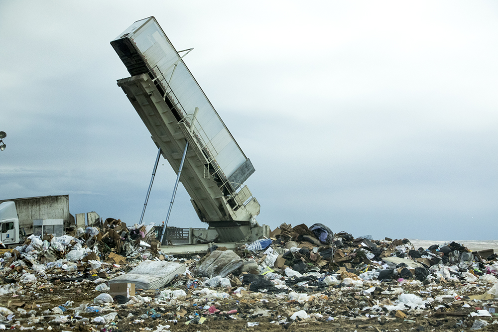 A truck is inverted atop the active dumping site. Denver Arapahoe Disposal Site, the landfill owned by Denver and operated by Waste Management. Jan. 26, 2018. (Kevin J. Beaty/Denverite)  waste management; garbage; environment; trash; dump; landfill; denverite; kevinjbeaty; colorado; aurora;