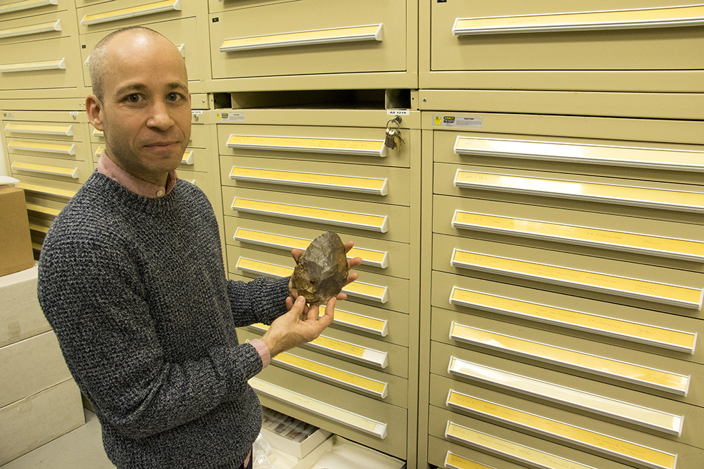 Denver Museum of Nature and Science curator Dr. Chip Colwell holds a 1.7-million-year-old hand axe found in Saudia Arabia, Jan. 29, 2018. (Kevin J. Beaty/Denverite)  denver; colorado; denverite; kevinjbeaty; dmns; denver museum of nature and science; science; archaeology;