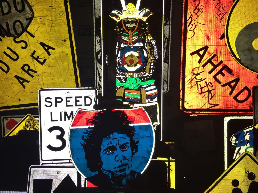 A portrait of Bob Dylan on an interstate sign by Dan Ericson. (Andrew Kenney/Denverite)