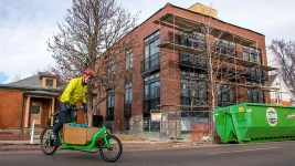 Ben Schumacher and his formidable cargo bike near a controversial construction project on South Pearl Street, Feb. 6, 2018. (Kevin J. Beaty/Denverite)