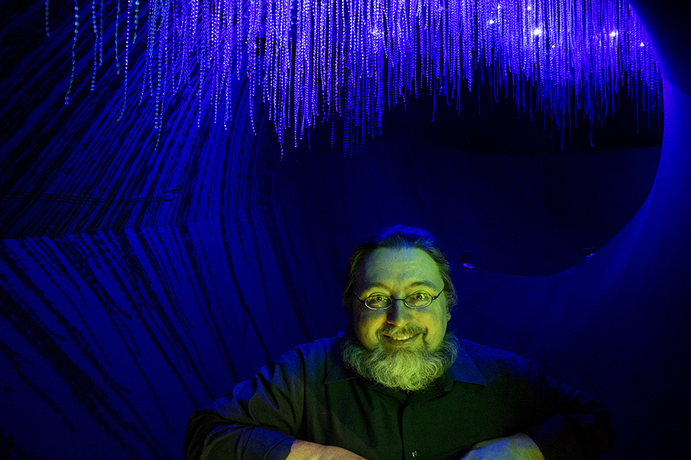 "Dr. Frank Krell poses inside a part of the ""Creatures of Light,"" exhibit at the Denver Museum of Nature and Science, Feb. 15, 2018. (Kevin J. Beaty/Denverite)"