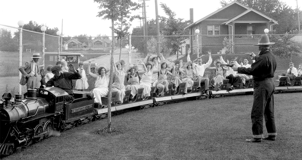 Passengers ride a miniature train at Elitch Gardens, Denver, Colorado, riding a miniature train. A man in bandit costume points guns at the passengers, circa 1920. (George Beam/Denver Public Library/Western History Collection/GB-5791)  elitch gardens; amusement park; archival; denver; denverite; kevinjbeaty; colorado;