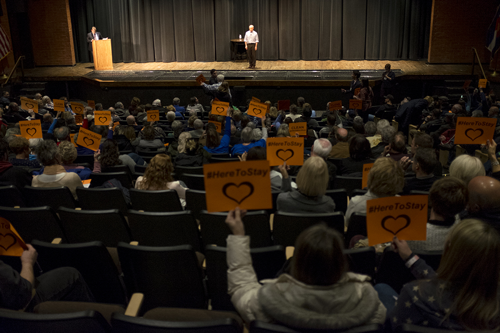"The crowd holds signs for a ""clean DREAM act"" as Mike Coffman speaks at a town hall event at Cherry Creek High School, Feb. 21, 2018. (Kevin J. Beaty/Denverite)  copolitics; town hall; mike coffman; greenwood village; denver; colorado; denverite; kevinjbeaty;"