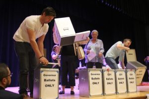 Volunteers turn ballot boxes over to show they're empty on March 24, 2018, at South High School.  (Esteban L. Hernandez/Denverite)