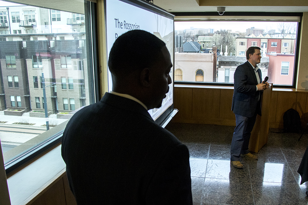 Development partner Haroun Cowans (left) listens to Palisade Partners President Paul Books speak as they meet with the Five Points community to announce new plans for the Rossonian Hotel. Blair-Caldwell African American Research Library, April 16, 2018. (Kevin J. Beaty/Denverite)  denver; colorado; denverite; five points; development; welton street; kevinjbeaty;