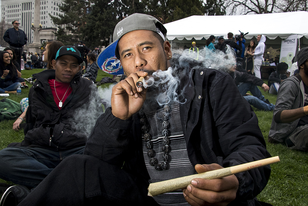 A member of the Twizted Kaskezt car club from Greeley, who asked not to be named, smokes a huge joint while holding a huge joint. Denver's 2018 Mile High 420 Festival, April 20, 2018. (Kevin J. Beaty/Denverite)  420; stoner; denver; denverite; colorado; kevinjbeaty;