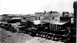 Teams of oxen pull wagons, one loaded with a horizontal tubular boiler, on Larimer Street in downtown Denver, circa 1863. (Western History & Genealogy Dept./Denver Public Library)