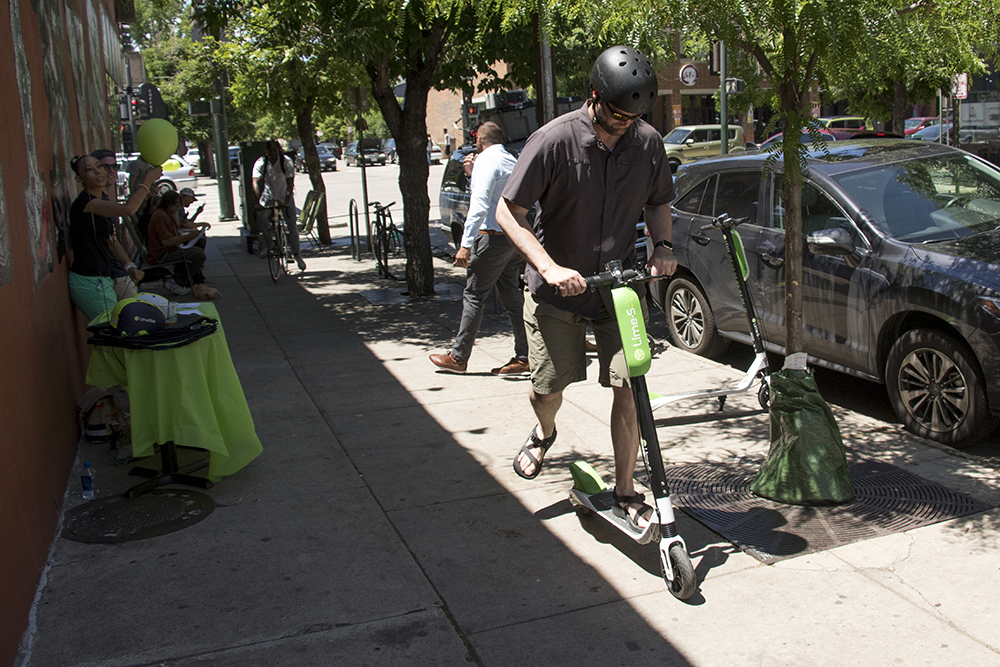 City Councilman Jolon Clark checks out Lime's new dockless electric scooters outside of Mutiny Information Cafe, May 25, 2018. (Kevin J. Beaty/Denverite)