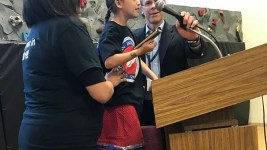 Tanski Chrisjohn gets help adjusting the microphone at a school board meeting from Denver Superintendent Tom Boasberg. (Melanie Asmar/Chalkbeat)