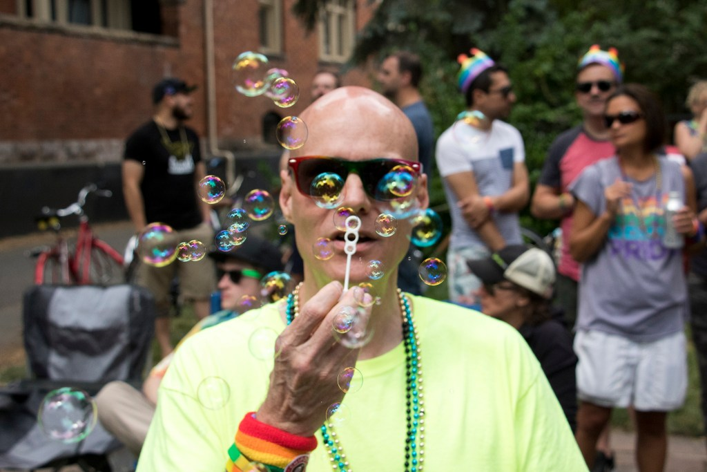Kent McFadden blows bubbles along the Denver PrideFest parade route, June 17, 2018. (Kevin J. Beaty/Denverite)