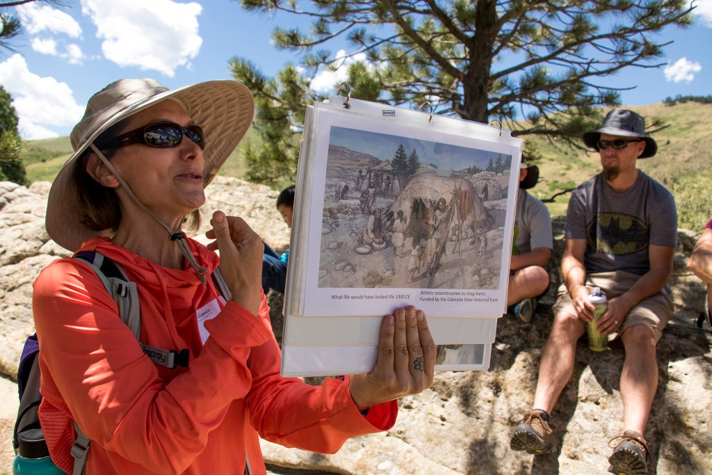 Lisa Yemma shows depictions of ancient life on her tour of Magic Mountain, an archaeological dig site run by Michelle Koons of the Denver Museum of Nature and Science, June 22, 2018. (Kevin J. Beaty/Denverite)
