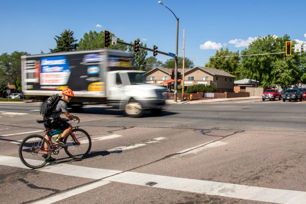 A cyclist waits to ride through the intersection of 26th Avenue and Wadsworth Boulevard in Wheat Ridge, July 3, 2018. (Kevin J. Beaty/Denverite)