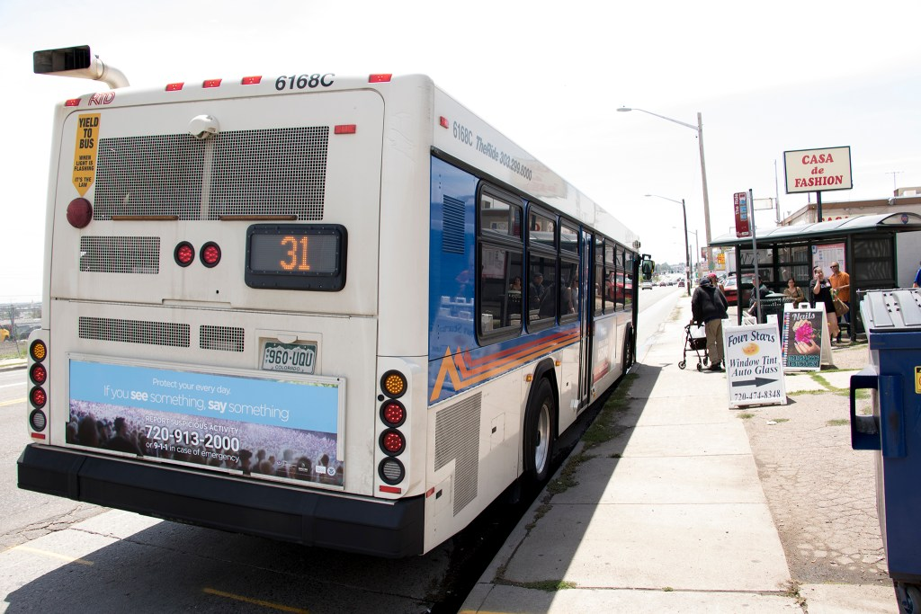 A bus picks up passengers along Federal Boulevard, July 20, 2018. (Kevin J. Beaty/Denverite)