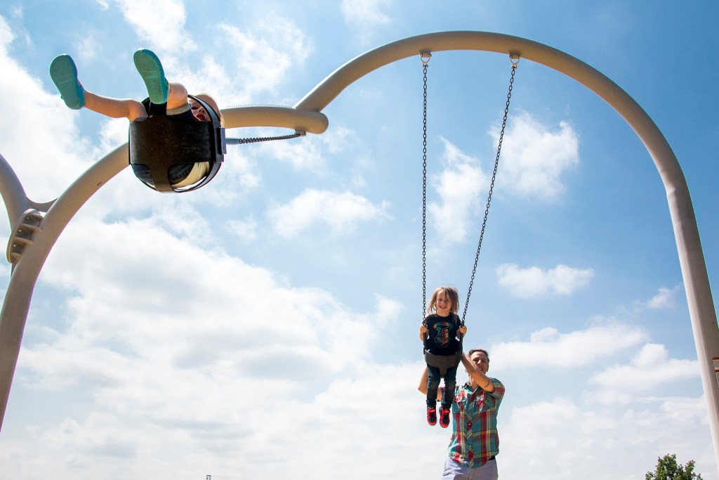 Patrick Kelsall pushes his kids, Oriole (left) and Aster on swings at Paco Sanchez Park, July 26, 2018. (Kevin J. Beaty/Denverite)