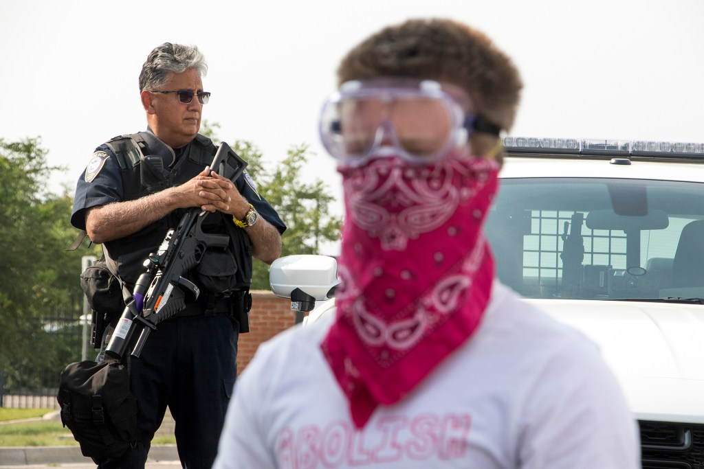 A U.S. Department of Homeland Security police officer stands with a large weapon as immigration activists rally in front of the Jim Bailey Building, local headquarters for U.S. Immigrations and Customs Enforcement in Centennial, Aug. 2, 2018. (Kevin J. Beaty/Denverite)