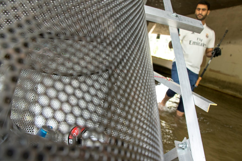 Muaath Albadin peers over a trash-eating water wheel on the Cherry Creek that's pushing a Coke bottle into a bag, Aug. 20, 2018. (Kevin J. Beaty/Denverite)