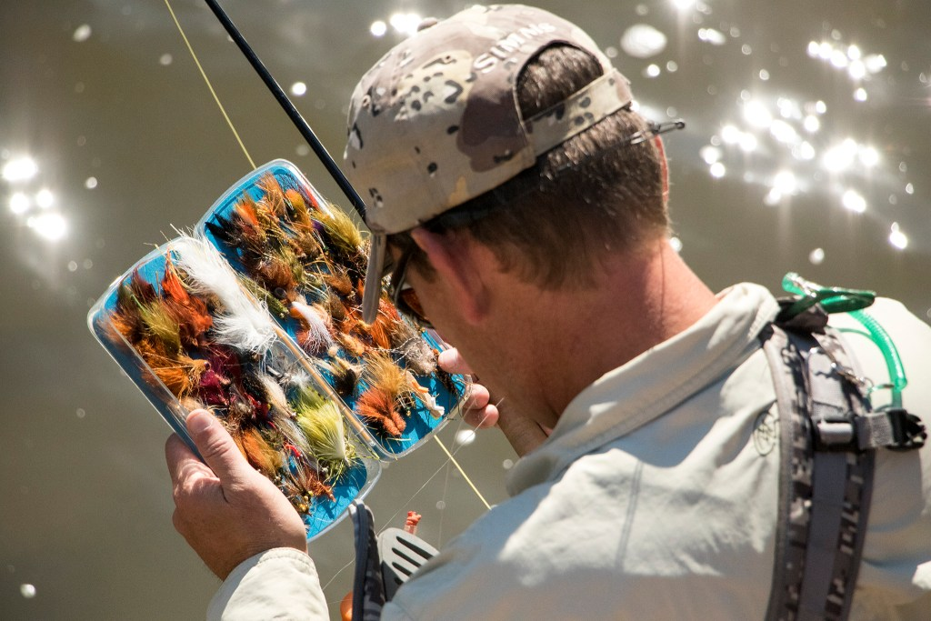 Barry Howsden sorts through fly lures as he hunts for carp. Denver Trout Unlimited's 12th annual Carpslam flyfishing tournament on the South Platte River, Sept. 9, 2018. (Kevin J. Beaty/Denverite)