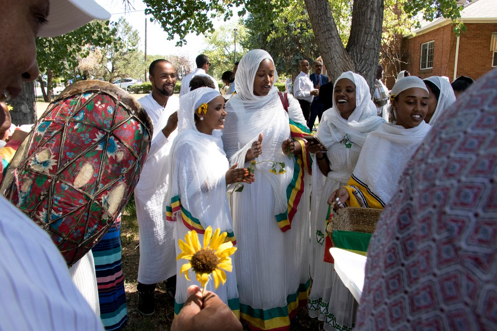 Women play drums, distribute flowers and collect alms outside of St. Mary Ethiopan Orthodox Church after an Ethiopian New Year service. Aurora, Sept. 9, 2018. (Kevin J. Beaty/Denverite)