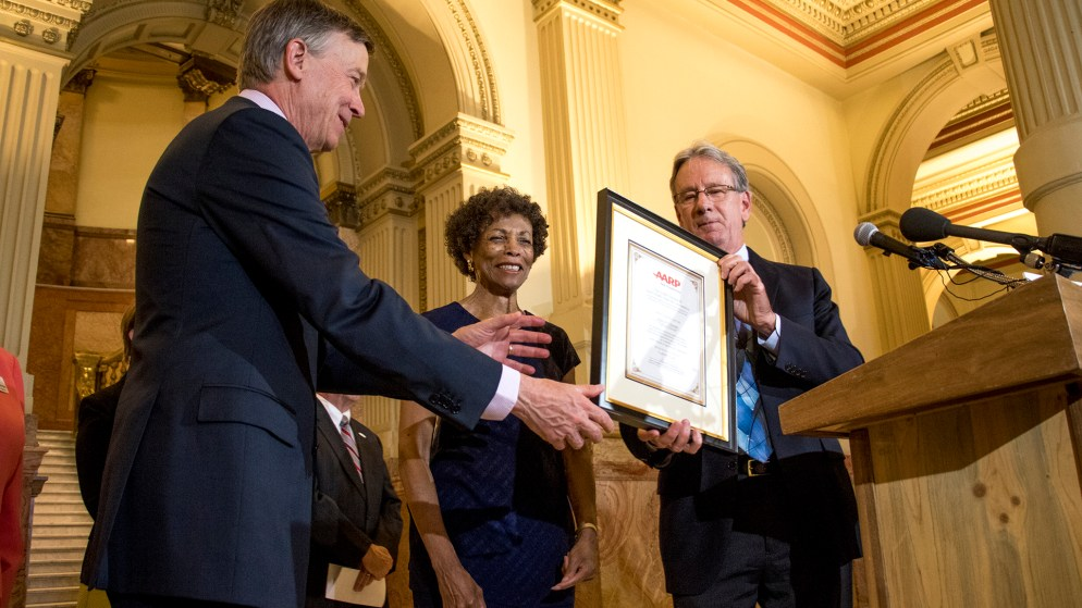 Bob Murphy, AARP Colorado state director (right to left), and Jean Nofles, AARP Colorado state president hands a framed recognition to Governor John Hickenlooper, Sept. 18, 2018. (Kevin J. Beaty/Denverite)