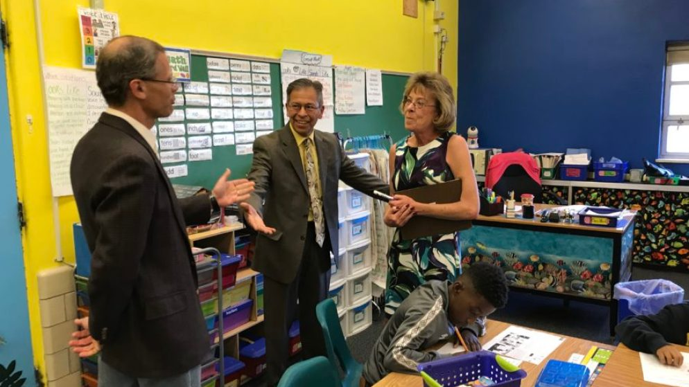 Denver Superintendent Tom Boasberg tells Stedman Elementary teacher Dawn Romero that her former principal, Ron Cabrera, center, is the new interim superintendent. (Melanie Asmar/Chalkbeat)