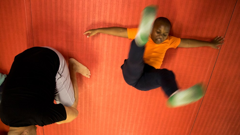 Skiler (7) learns how to fall safely during boxing class at Heavy Hearts Heavy Hands gym in Aurora, Oct. 17, 2018. (Kevin J. Beaty/Denverite)