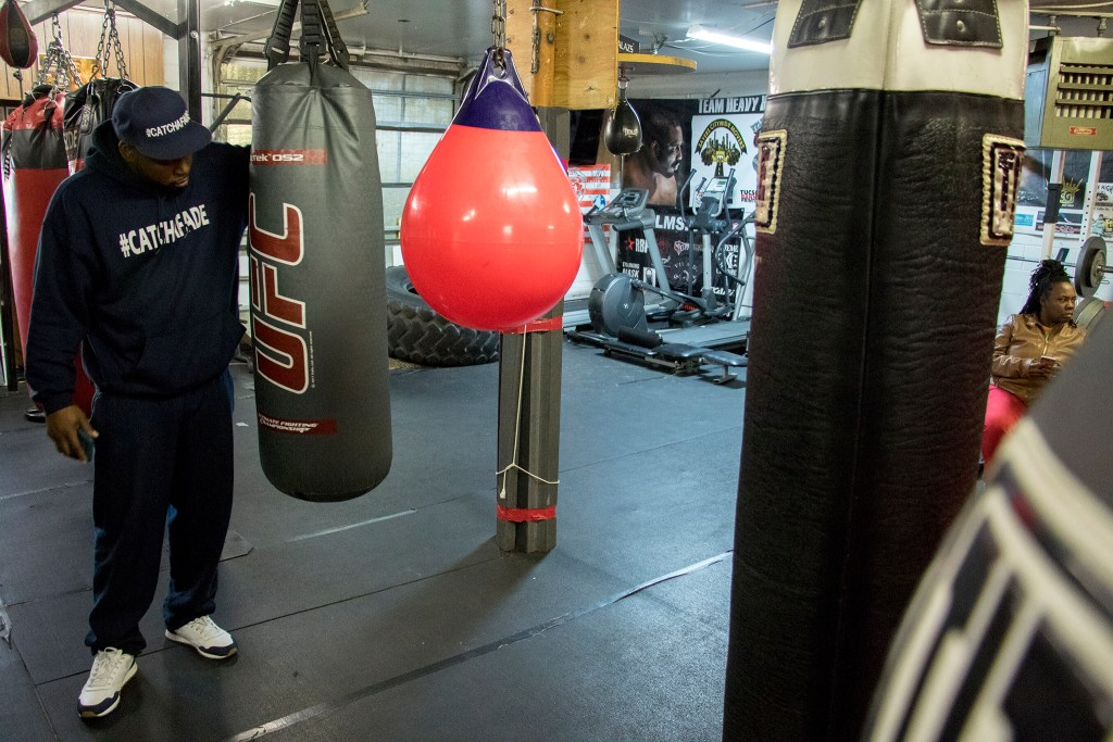 Dontae Hudspeth inspects a punching bag inside Heavy Hearts Heavy Hands gym in Aurora, Oct. 17, 2018. (Kevin J. Beaty/Denverite)