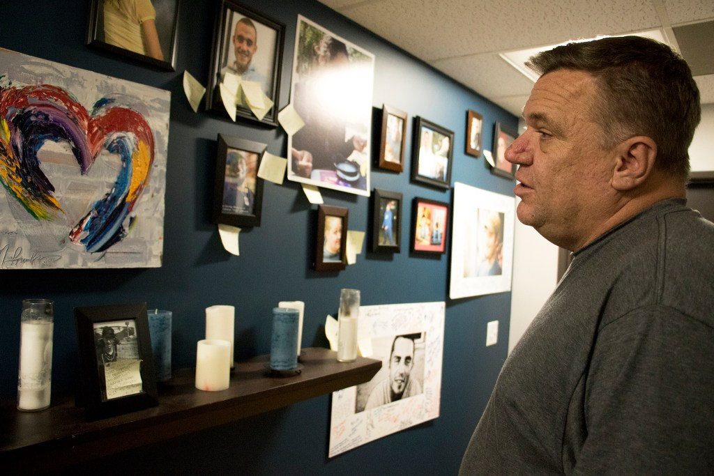 Robbie Goldman, co-director of Dry Bones Denver, stands beside a wall of portraits of members who have passed away, Oct. 18, 2018. (Kevin J. Beaty/Denverite)