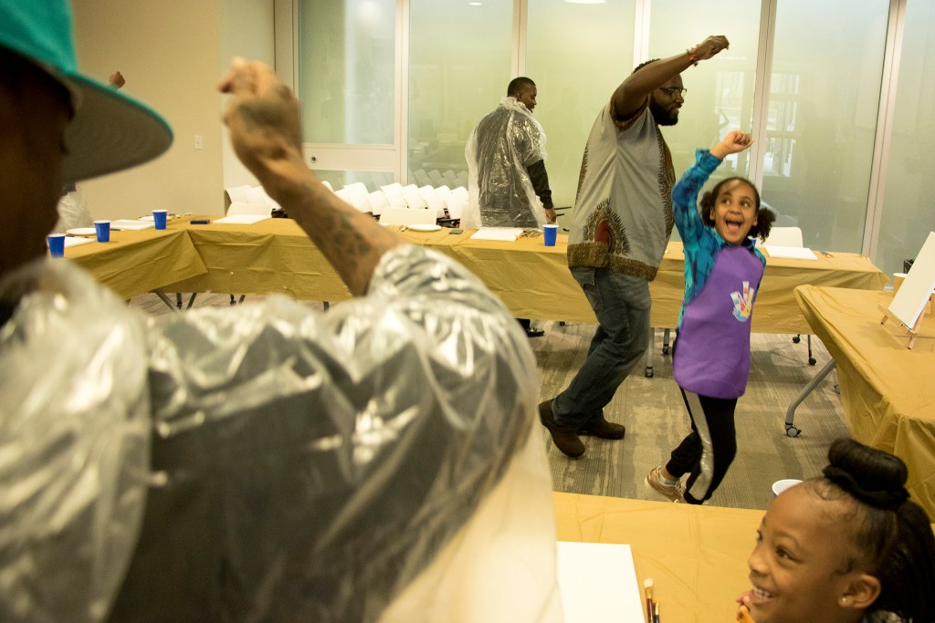 Joseph Graves and his daughter, Rory (7), help a painting class get the wiggles out during A Father Daughter Occasion at the Dahlia Campus for Health and Well-Being in Northeast Park Hill, Oct. 27, 2018. (Kevin J. Beaty/Denverite)