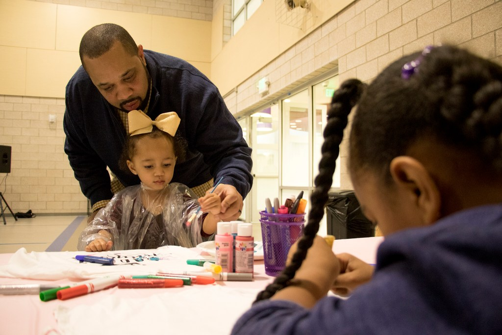 Herman White and his daughter, Kyndall (2), paint t-shirts during A Father Daughter Occasion at the Dahlia Campus for Health and Well-Being in Northeast Park Hill, Oct. 27, 2018. (Kevin J. Beaty/Denverite)