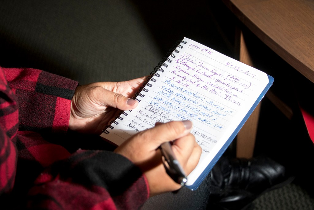 Katelyn Puga signs a book inside Metro State University's honors program building, which was written in previously by her grandmother and cousin. The office used to be her family's home, and is now part of the Auraria Ninth Street Historic District, Oct. 30, 2018. (Kevin J. Beaty/Denverite)