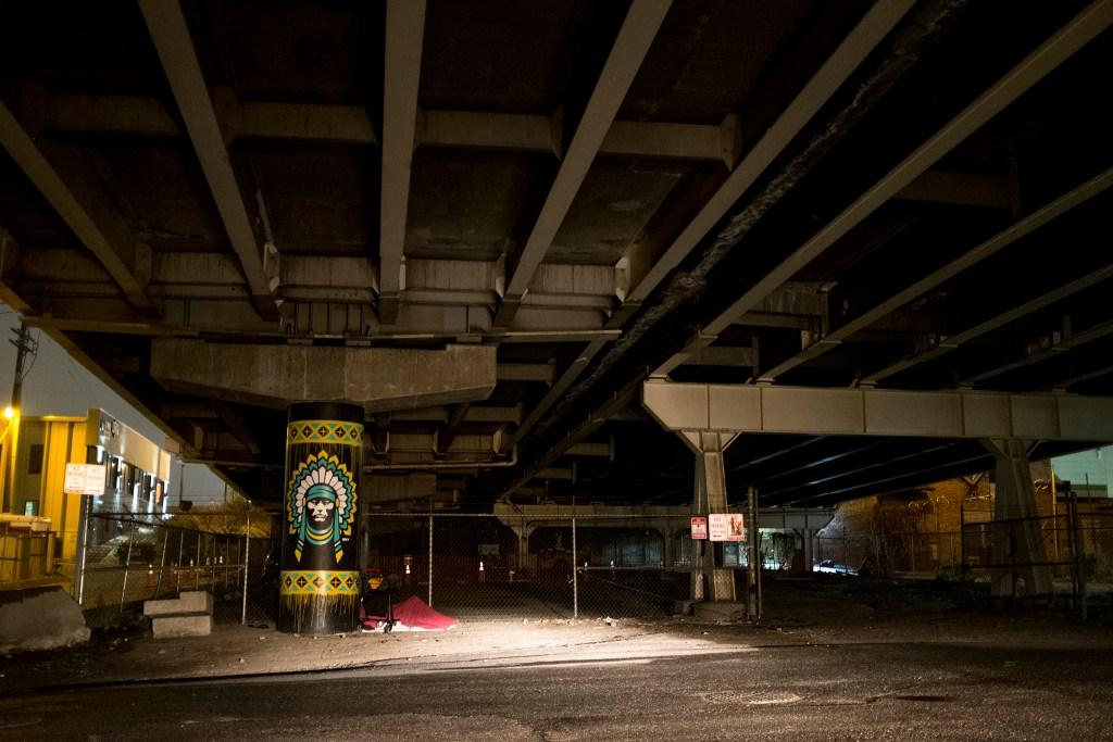 A woman sleeps under a bridge in Baker, Oct. 30, 2018. (Kevin J. Beaty/Denverite)