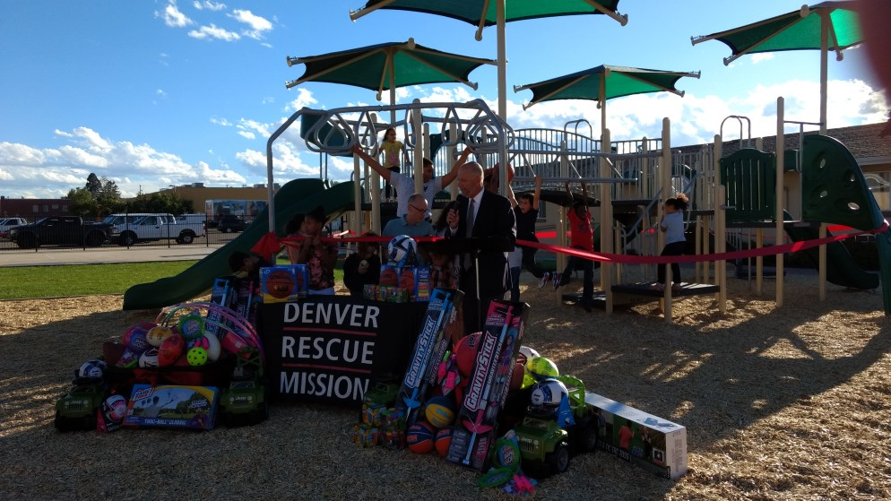 Denver Rescue Mission President and CEO Brad Meuli, at podium, inaugurates a new playground at his non-profit's transitional shelter for families. (Donna Bryson/Denverite)