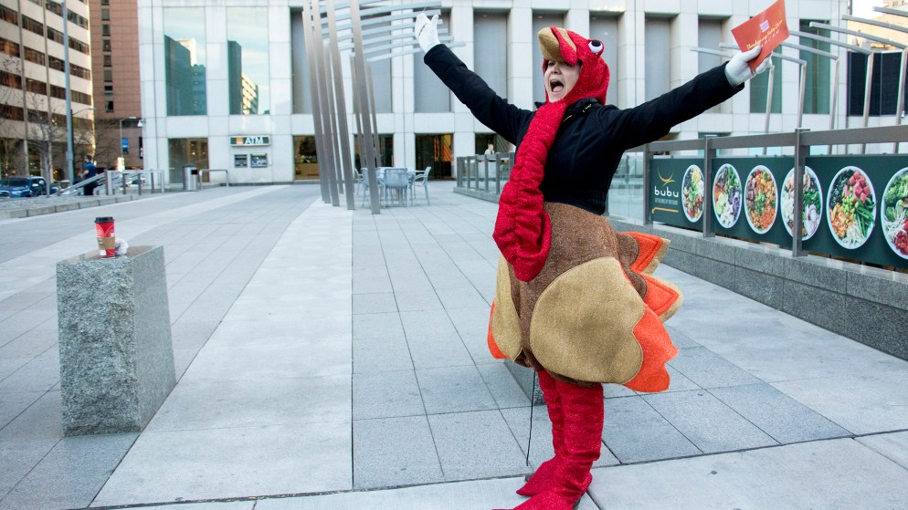 Alexxa Gagner, director of public relations for Denver Rescue Mission, celebrates the first donation of their holiday turkey drive outside of Republic Plaza, Nov. 2, 2018. (Kevin J. Beaty/Denverite)
