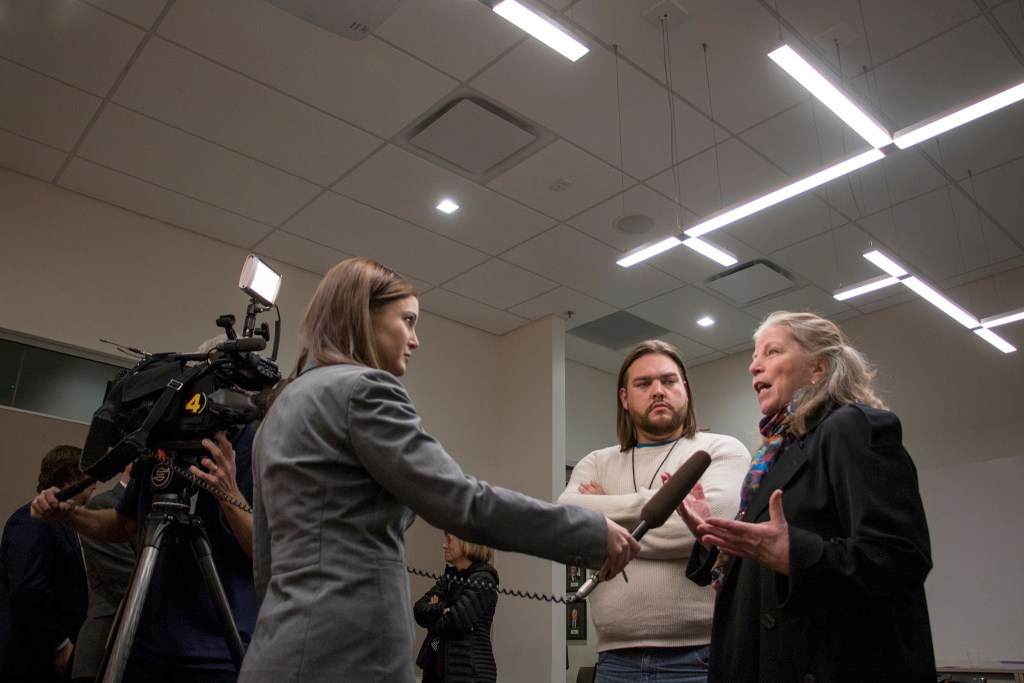 Ean Tafoya and Becky English speak with a news crew after the Colorado Transportation Commission agreed to a settlement in the third and final lawsuit against the I-70 widening project, Dec. 20, 2018. (Kevin J. Beaty/Denverite)