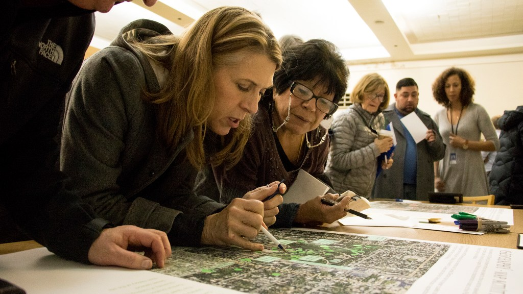 Rev. John Hill (left to right), Sharon Hammond and Lupe Loyd check out a map of the Loretto Heights campus in Harvey Park South during a meeting about the area's future, Jan. 15, 2018. (Kevin J. Beaty/Denverite)