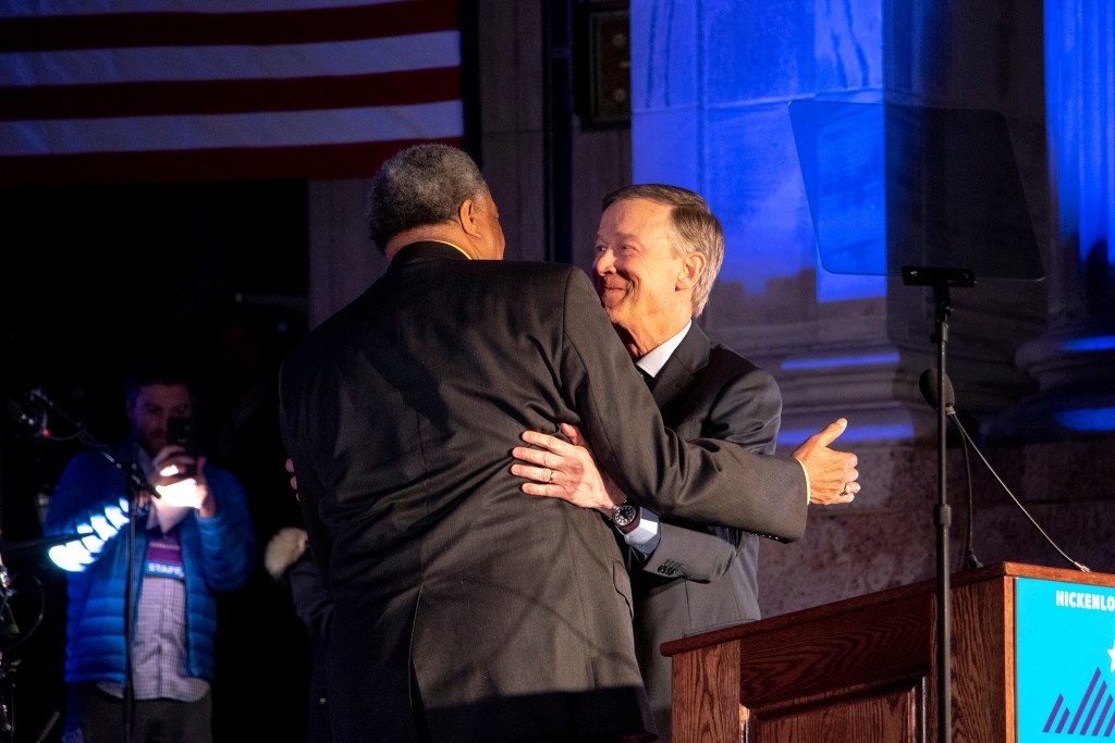 Former Denver Mayor Wellington Webb embraces John Hickenlooper before he addresses supporters for his run at the presidency during a rally at Civic Center Park, March 7, 2019. (Kevin J. Beaty/Denverite)