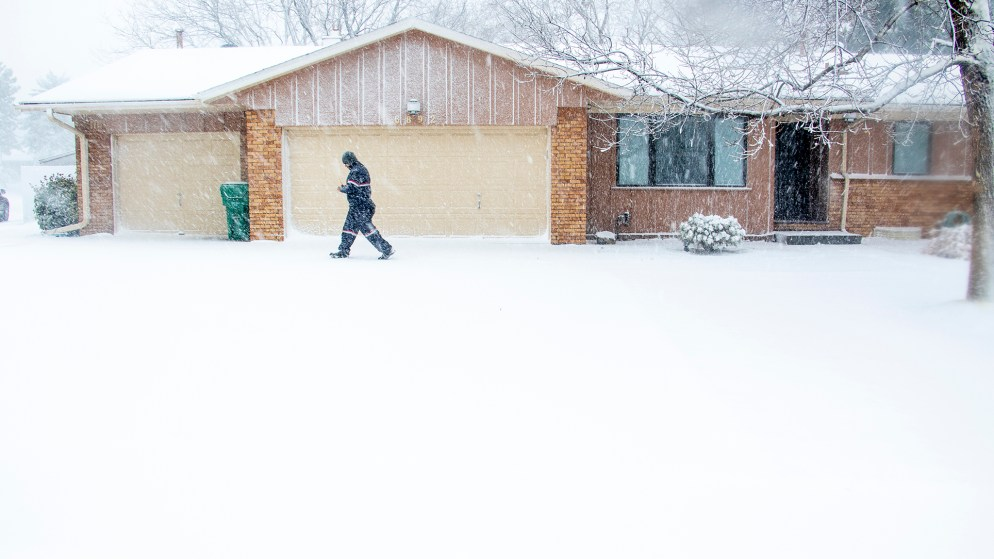 """Luis Sanchez walks part of his daily route in Denver's Goldsmith neighborhood during a """"bomb cyclone"""" blizzard, March 13, 2019. (Kevin J. Beaty/Denverite)"""