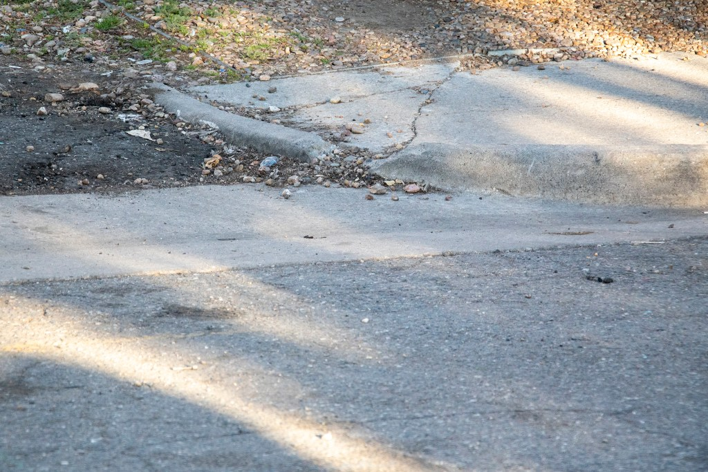 Some broken sidewalk that required Kayln Rose Heffernan to reroute on the way to the race's starting point. The Denver Streets Partnership's Amazing Denver Mobility Race, April 4, 2019. (Kevin J. Beaty/Denverite)