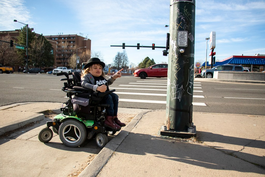 Mayoral candidate Kayln Rose Heffernan demonstrates her inability to activate a crosswalk on Colfax Avenue. The Denver Streets Partnership's Amazing Denver Mobility Race, April 4, 2019. (Kevin J. Beaty/Denverite)