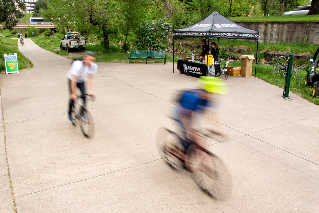 Cyclists speed by Denver Parks and Recreation's safety booth on the Cherry Creek Trail, May 16, 2019. (Kevin J. Beaty/Denverite)