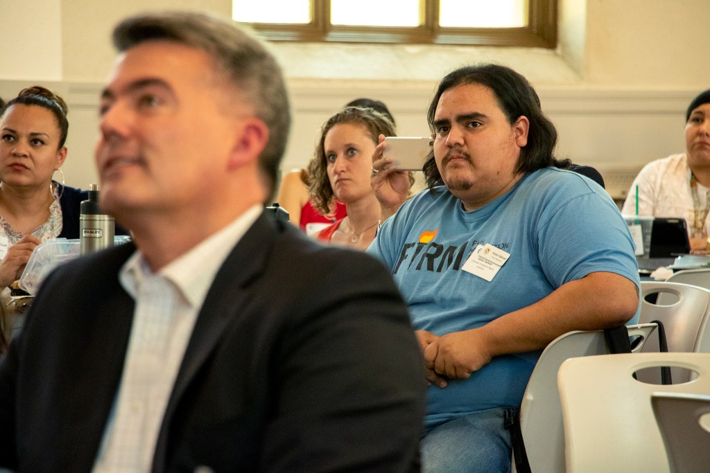 Victor Galvan, a member of the Colorado Immigrant Rights Coalition, listens a discussion on immigration behind U.S. Sen. Cory Gardner. St. Cajetan's church on the Auraria Campus, June 28, 2019. (Kevin J. Beaty/Denverite)