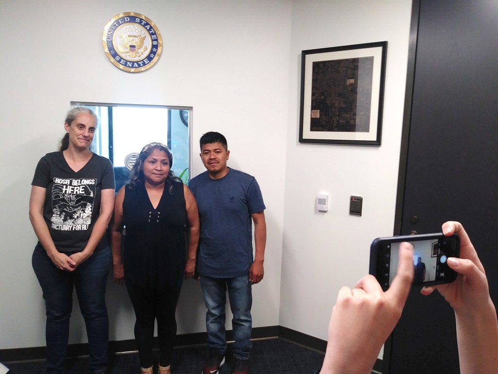 Madeline Quartaro, who works for Sen. Cory Gardner, agreed to photograph Jennifer Piper (left to right), Lupe Lopez and Jose Luis Garcia in Gardner's office. July 2, 2019. (Kevin J. Beaty/Denverite)
