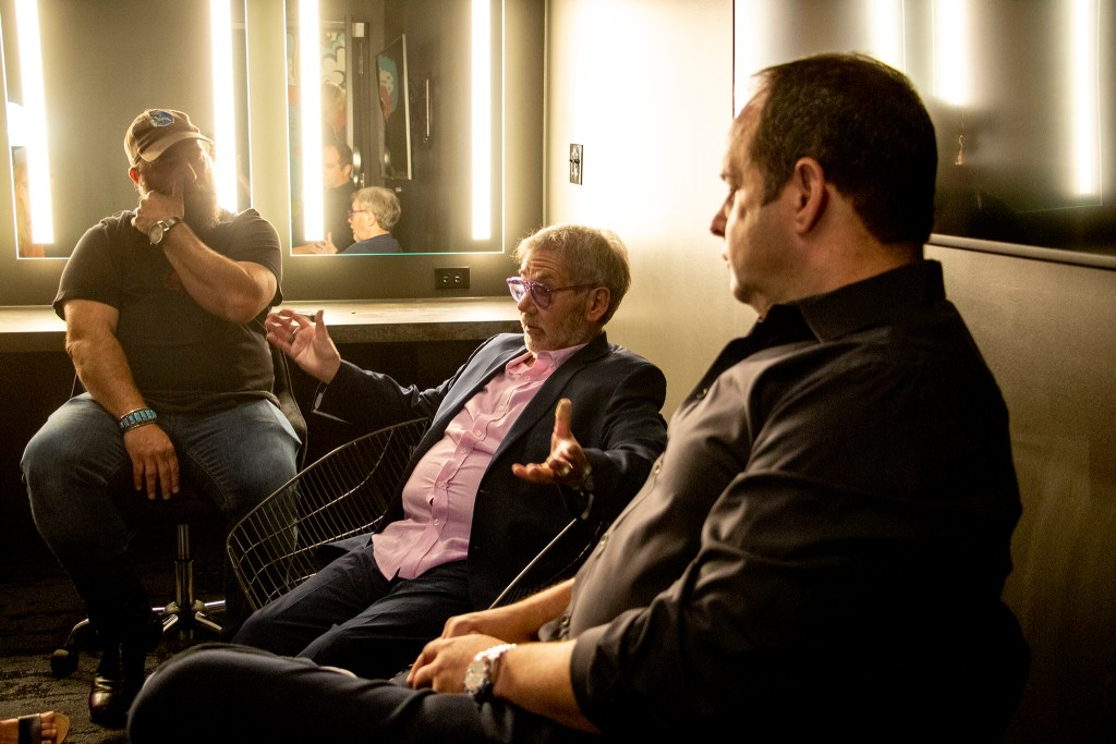 Don Strasburg, Chuck Morris and Brent Fedrizzi speak to a reporter inside a Mission Ballroom dressingroom. Elyria Swansea, RiNo, July 30, 2019. (Kevin J. Beaty/Denverite)