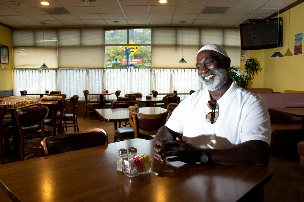 Flynn Dickerson speaks to a reporter in Welton Street Cafe, the restaurant he founded more than 35 years ago. Today, he's celebrating 20 years in this location. Five Points, July 30, 2019. (Kevin J. Beaty/Denverite)