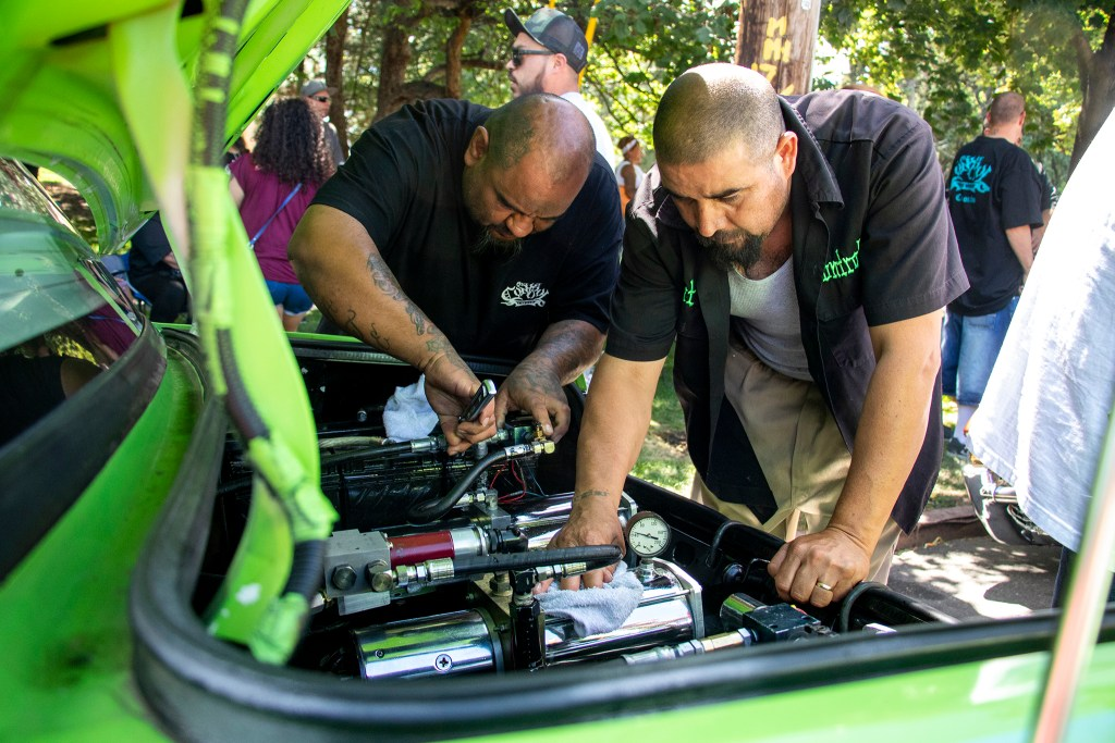 Avery Peinado and Juan Guzman work on a hydraulic system at La Raza (or Columbus) Park before a cruise down Federal Boulevard. Aug. 25, 2019. (Kevin J. Beaty/Denverite)