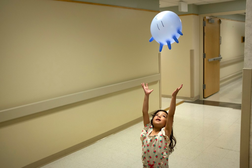 Armando Peniche-Cruz's granddaughter, Athena, plays with a rubber-glove balloon as he undergoes radiation treatment down the hall. July 18, 2019. (Kevin J. Beaty/Denverite)