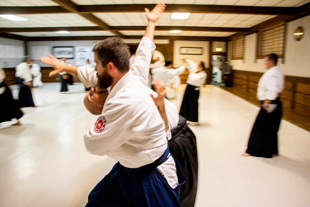 Aikido Nippon Kan instructor Jason Lowrey flips his partner during practice, Aug. 5, 2019. (Kevin J. Beaty/Denverite)